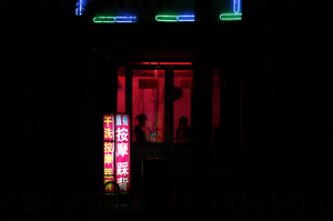 Two girls sit near the window of a massage salon on a street in the city of Weifang in Shandong Province