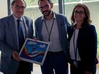 Il Presidente Tommaso Rossi e la Segretaria Mary Basconi consegnano al Dr. Tarfusser un dipinto a mano con l'effige dell'Associazione fatto preparare appositamente in occasione della visita a l'AIA.