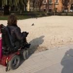 """Una signora in carrozzina a piazza Cavour, decide di non raggiungere l'angolo delle panchine per non rischiare di rimanere """"impantanata"""" nella ghiaia."""